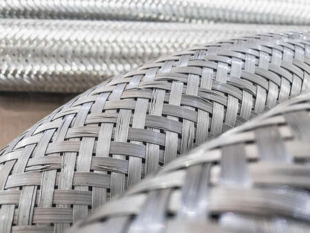 Long metal flexible compensator pipes metal texture closeup. Selective focus. White metal industrial construction.