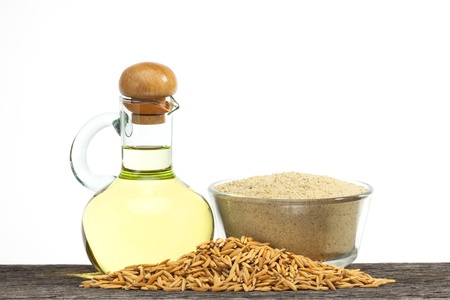 cooking oil: Rice bran oil in bottle glass with seed and bran on the old plank wood