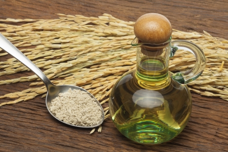 bran: Rice bran oil in bottle glass with seed and bran on the old plank wood