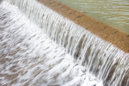 Water flows over a man-made waterfall at the edge of a Lake