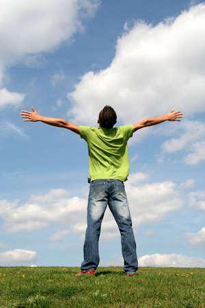 L'uomo in piedi su erba a braccia aperte