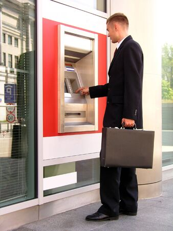Businessman using cash machine photo