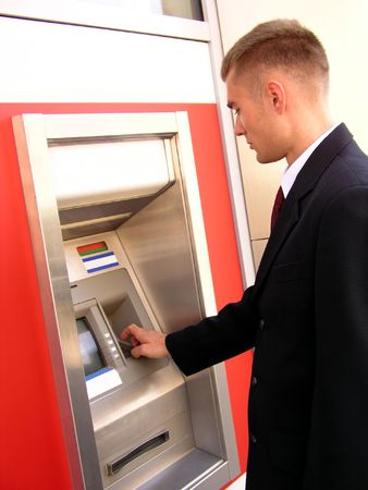 Businessman using cash machine photo