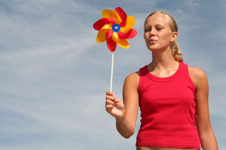 Young Woman Blowing Pinwheel Stock Photo - 484793
