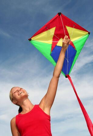 Happy Young Woman Flying a Kite photo