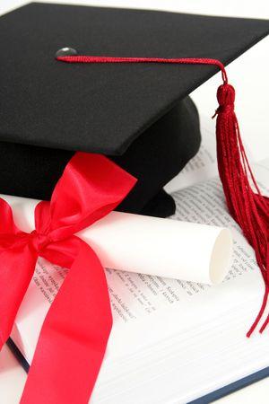 Graduation cap and diploma on a book Stock Photo - 627453