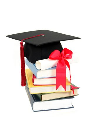 Cap and diploma on stack of books Stock Photo