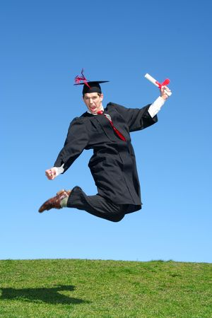 Male Graduate Leaping for Joy Outdoors photo