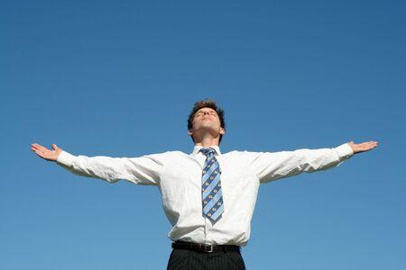 manos levantadas al cielo: El hombre de negocios con los brazos outstretched Foto de archivo