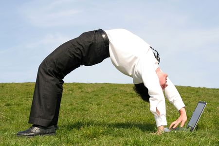 Businessman bending over backwards and using laptop Stock Photo - 899974