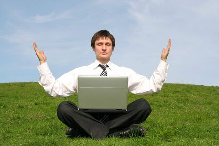 Businessman with laptop doing yoga