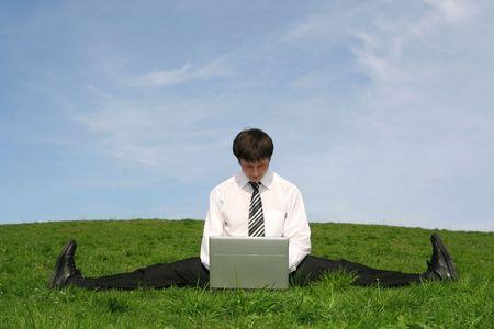 jambes �cart�es: homme daffaires faisant une fente et � laide de lordinateur portatif