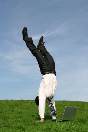 Businessman doing handstand and using laptop  photo