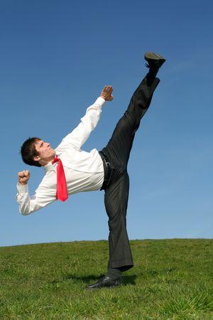 Businessman doing a karate kick outdoors photo
