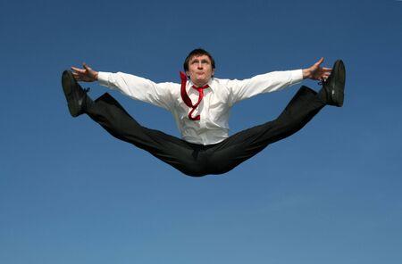 businessman doing splits in mid-air photo