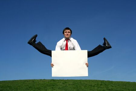 Businessman jumping and holding a blank sign photo