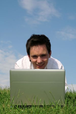 Young man using laptop outdoors photo