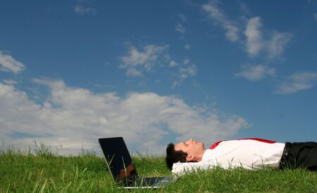 sun down: Businessman lying on the grass with laptop Stock Photo