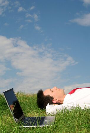 Businessman lying on the grass with laptop photo