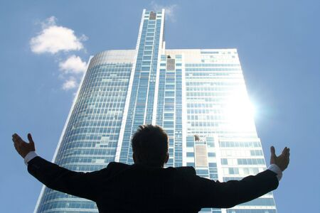 victorious: Businessman Raising Arms at Skyscraper
