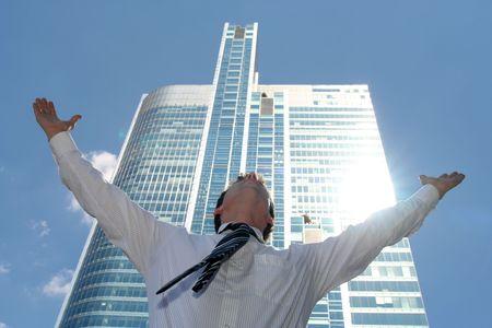 manos levantadas al cielo: Hombre de negocios que levanta los brazos en el rascacielos