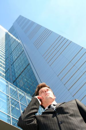 phonecall: Businessman on cellphone by skyscraper Stock Photo