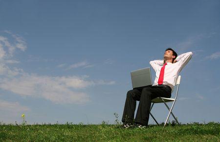 Businessman using laptop outdoors photo