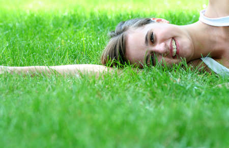 Beautiful young woman lying on a lawn  photo