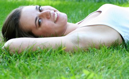 Woman lying on grass, smiling photo