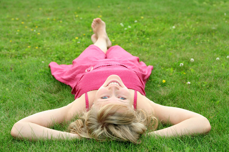 freetime: Woman lying on grass, smiling Stock Photo