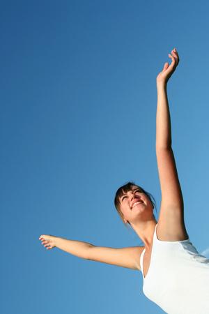 Woman spreading arms to sky photo