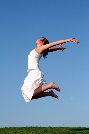 freetime: Happy woman jumping against blue sky Stock Photo