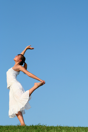 Young woman dancing on grass photo