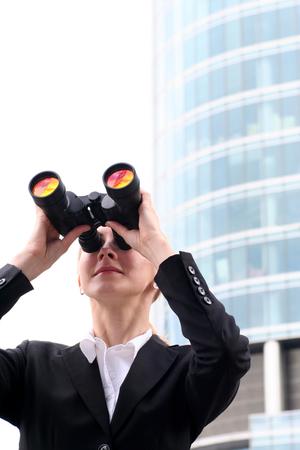 distant work: Businesswoman looking through binoculars
