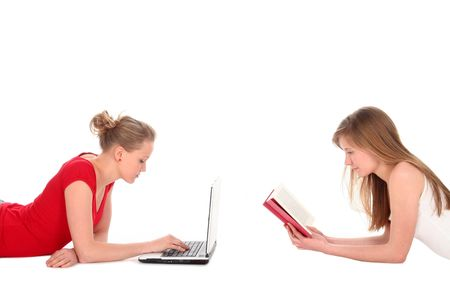 Young women reading book and using laptop photo