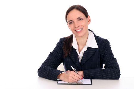 Businesswoman sitting at desk, writing photo
