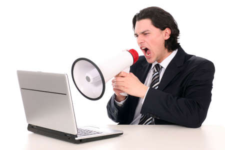 Businessman shouting through megaphone, sitting in front of laptop Stock Photo