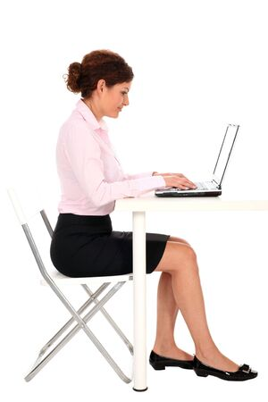sitting at table: Businesswoman using laptop