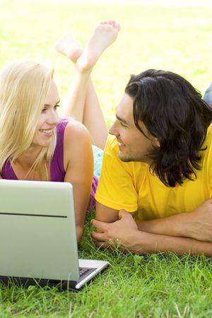 Couple using laptop outdoors photo