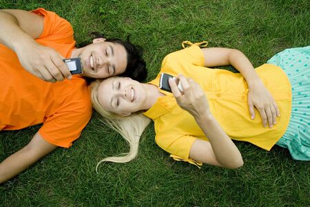 Couple lying on the grass with mobile phones
