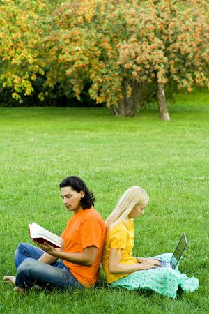 Students studying together, on grass photo