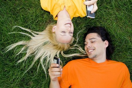mobile telephones: Couple lying on the grass with mobile phones