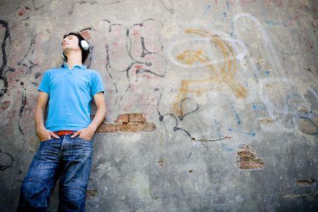 so�ando: El hombre recostado contra la pared con graffiti