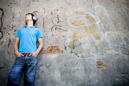 Man leaning against wall with graffiti photo