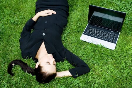 Businesswoman lying on grass with laptop 版權商用圖片
