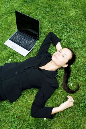 Businesswoman lying on grass with laptop Stock Photo - 3453809