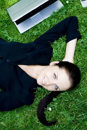 Businesswoman lying on grass with laptop Stock Photo - 3453804
