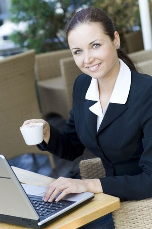 Woman with laptop drinking coffee photo