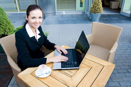Woman outside a restaurant with a laptop  photo
