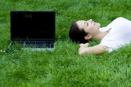Woman lying on grass with laptop photo